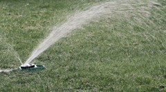 A sprinkler watering green lawn Stock Footage