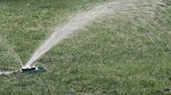 Stock Video Footage of A sprinkler watering green lawn
