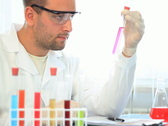 Scientist examine test tubes with chemicals and writing results NTSC Stock Footage