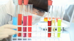 Scientist examine test tubes with chemicals and writing results on laptop HD Stock Footage