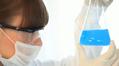 Female scientist looking at Erlenmeyer flask with blue substance, steadicam shot Stock Footage