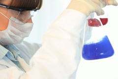 Scientist looking mixing chemicals in Erlenmeyer flask, steadicam shot NTSC Stock Footage