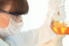 scientist looking at volumetric flask with yellow substance, steadicam shot - stock footage
