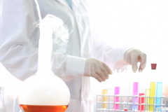 Female scientist examinines test tubes with smoky Volumetric Flask in front Stock Footage