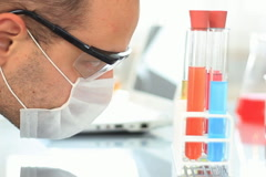 Scientist looking at test tubes in stand and writing results on laptop NTSC Stock Footage