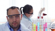 Portrait of male scientist in laboratory, female coworker in background HD Stock Footage
