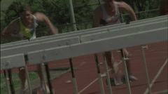 A group of men jump hurdles on a running track. Stock Footage