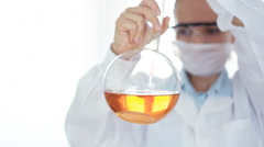 Female scientist pouring red substance from pippete into Volumetric flask HD Stock Footage