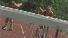 A group of women run and jump over hurdles. - stock footage