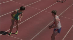 Male runners pass the baton in a relay race. Stock Footage