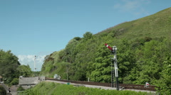 Old English diesel train and carriages pass by hills and stone house Stock Footage
