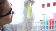 Scientist looking at test tubes with colorful chemicals HD Stock Footage