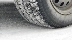Car starts drifting wheel closeup on snowy road Stock Footage