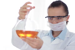 Female scientist mixing chemicals in volumetric flask NTSC - stock footage