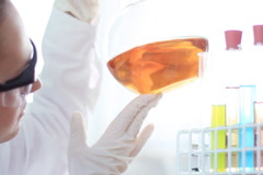 Female scientist mixing chemicals in volumetric flask NTSC Stock Footage