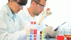 Scientists looking at test tubes and writing results on clipboard HD Stock Footage
