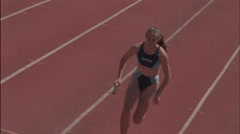 Stock Video Footage of A female runner passes the baton in a relay race.