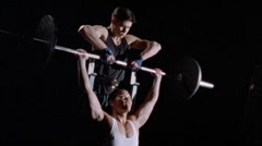A weight lifter gets assistance from a spotter. Stock Footage