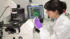 Scientist looking through microscope and check results on screen - stock footage