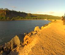 PAN Molokai ocean pond, pan left and back, white rocks, mountains Stock Footage