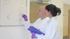 Scientist analyze and discuss research data on white board in science laboratory - stock footage