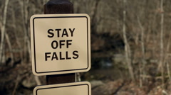 Rack focus of stay off falls sign Stock Footage