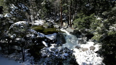 Water flowing through mountain rocks with snow Stock Footage