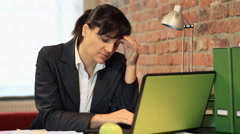 Businesswoman working on laptop having headache - stock footage