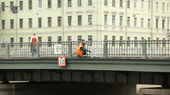 Worker in orange clothes paints bringe railing. Timelapse Stock Footage