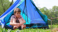 Boy with bare feet sits in tent at forest Stock Footage
