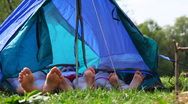 Family with bare feet lies in tent at forest on day, and then boy sits Stock Footage