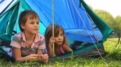 Boy with girl lay peeping out of tent, he something says at forest Stock Footage