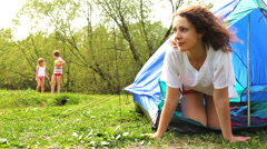 Woman looks out from tent on two kids, then they come and pull cord at forest Stock Footage