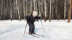 Young boy bounces on skis, pushing off sticks Stock Footage
