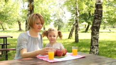 Mother and daughter eat and drink Stock Footage