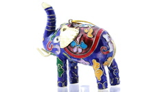 Souvenir elephant painted in oriental style stands on rotating glass Stock Footage