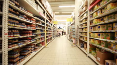 Stands with food in hypermarket, shooting from fast moving between them camera Stock Footage