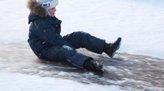Boy sitting on sled moves down for ice slide Stock Footage