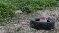 Old tire on the ground with construction cone Stock Footage