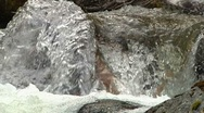 Dancing mosiac of water rushing over wood and stone (audio included) Stock Footage