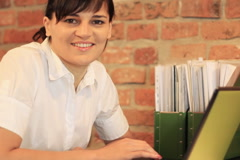 Young businesswoman working on laptop and smiling to camera, steadicam shot Stock Footage