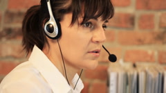 Attractive helpdesk consultant talking on headset HD Stock Footage