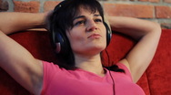 Happy woman on sofa listening music, steadicam shot HD Stock Footage