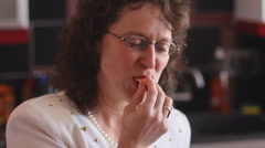 Middle aged woman eating and drinking various things while in the kitchen - 8 Stock Footage