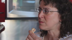 Middle aged woman eating and drinking various things while in the kitchen - 7 Stock Footage