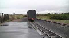 Old English steam train and carriages leaving small railway station near beach Stock Footage