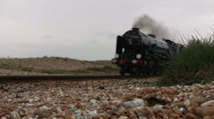 Old English steam train and carriages passing near beach Stock Footage