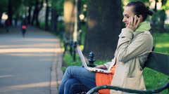 Woman with laptop and mobile phone sitting in the park, steadicam shot HD Stock Footage