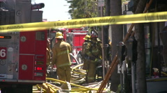 Firefighters at Work next to firetruck at a fire scene Stock Footage