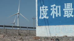Huge characters, wind turbines, Chinese trucks Stock Footage
